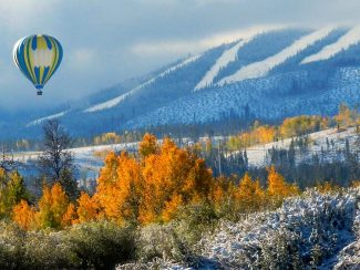 A balloon flies over fall colors and the early season snow at Winter Park Resort.
