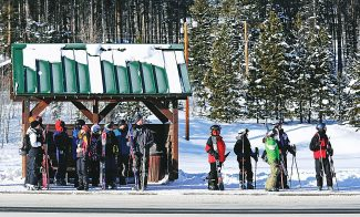 Skiers and snowboarders wait for a shuttle bus in downtown Winter Park during December 2012.