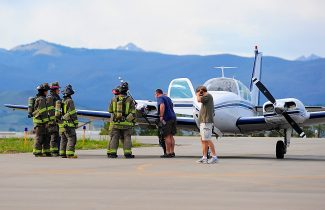 Granby Fire Department fire fighters examine a plane that had to make an emergency landing at the Granby Airport on Tuesday afternoon, July 9.  The plane, a twin-engine Beechcraft Baron owned by Sage Aviation of Grand Junction, reported a leak from one of the engines while in flight.  The plane landed in Granby without incident and the pilot and two passengers exited the plane safely.  Byron Hetzler/Sky-Hi News