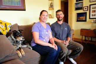 Jessica and Christian Smolleck pose in their home with their dog, Callie.  Byron Hetzler/Sky-Hi News