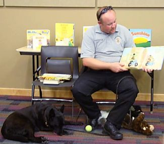 Brett Schroetlin from the K9 unit of the Winter Park/Fraser Valley Police Department reads to Granby Library story hour participants recently with his dog Argo.
