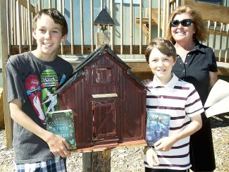 """Indian Peaks Charter School 7th-graders Akram Hanna (from left) and Zane Schuessler, with teacher Vickie Simpson, proudly display the """"Little Free Library"""" they created in front of the school. The books within are free and available to anyone."""