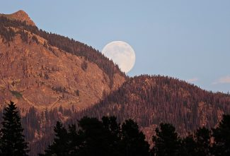 A nearly full moon rises from behind the Continental Divide as seen from Grand Lake on Sunday evening, July 21.