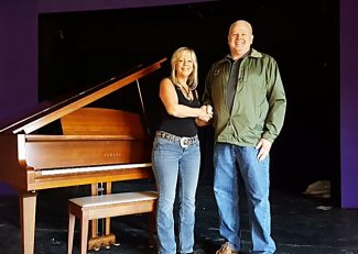 Peggy Mann and Mike Brown of Grand Lake stand next to the recently donated baby grand piano at The Grand Lake Community House.