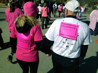 Participants in the run/walk to end all cancer in Grand Lake on Sunday, Sept. 29, wore signs in celebration, or in memory, of loved ones.
