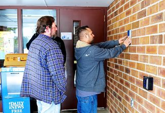 John Weninger of the East Grand School District, left, and Rick Garcia of Tyco Integrated Systems look at possible locations for a new entrance security system for the entrance doors at Granby Elementary School on Thursday, Feb. 13.