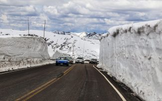 Cars pass through a canyon of snow on top of Trail Ridge Road in Rocky Mountain National Park, on Sunday, May 29.