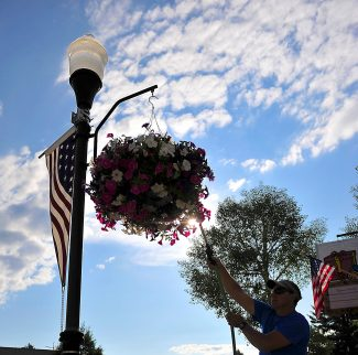 Town of Granby employee Peter Butrymovich waters the flowers along Agate Avenue in Granby on Thursday morning, July 4.  Byron Hetzler/Sky-Hi News