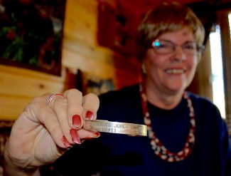 Sue Held displays a bracelet given to her by American Airlines after 9/11. The bracelet commemorates her brother's presence on Flight 11 that morning. Sue carries it with her almost everywhere she goes as a subtle reminder of what she, and others, lost that tragic day.