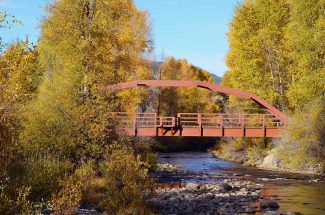The bridge over the Fraser River just outside Kaibab Park in Granby is framed by thick golden foliage. Aspens and cottonwood trees line the Fraser River along the southern end of Granby and offer quality leaf peeping close to town.