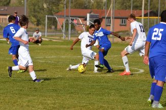 Soccer players from Middle Park (in white) work to contain an opposing player during match play in Granby Wednesday evening against the Sheridan Rams.