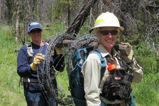 Doreen Sumerlin (front), Wildlife Biologist with the USFS, works with Michelle Cowardin from Colorado Parks and Wildife to remove barbed wire fencing from the Buffalo Creeek area as part of a volunteer project this summer.
