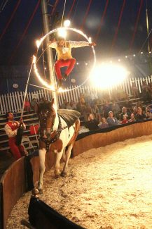 An equestrian performer entertains the crowd by jumping through a ring of fire during the Zoppe Family Circus on Saturday, September 3 in Fraser.
