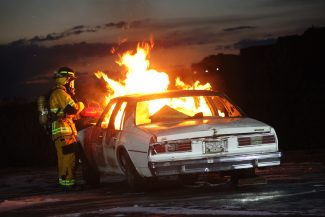 Firefighter, Banning Starr, uses a drip torch to light a car on fire during training at the East Grand Fire Station in Fraser on Tuesday, August 15.