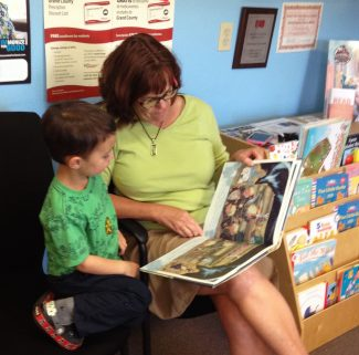 Brene Belew-LaDue, Director of Grand County Public Health, is reading to Harry Banks.