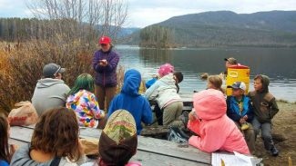 Polly Gallagher (standing center), Outdoor Education, Wellness and Leadership Program Director for IPCS, goes over a lesson with students from Indian Peaks on the shores of Shadow Mountain Lake.