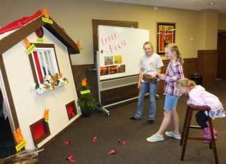 Peyton Olson cheers on a young visitor as she throws ping pong balls disguised as flaming embers at the Ember House on Tuesday, October 4 during the Fire Prevention Week Open House in Granby.