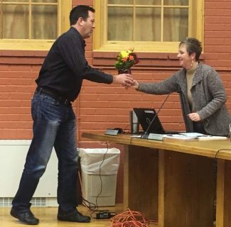 Fraser Town Manager Jeff Durbin hands Town Clerk Lu Berger flowers at Berger's last Town Council meeting on October 19.