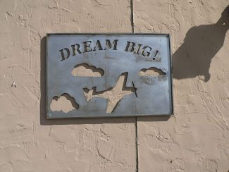 "Tabernash metal artist, Taylor Quick, designed, cut, and donated this unique ""Dream Big- sky and airplane"" steel sign for the outside of the former Rocky Mountain Airways airline terminal at 1023 CR 610 at Granby/Grand County Airport-Emily Warner Field so that all could easily see and enjoy the art and message. Over time the steel will rust and become a beautiful shade of brown. Quick hung the heavy sculptured sign with the help of Lane Meeks, Jocille Quick and Penny Hamilton, all dedicated Grand County Historical Association aviation museum volunteers."