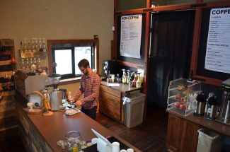 Jayson Harris, owner of The Perk, prepares for the morning coffee rush.