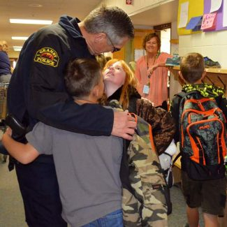 Granby Chief of Police Bill Housley is hugged by two students from Granby Elementary School Monday morning Nov. 14 as the students make their way to class at the beginning of the day. Chief Housley typically greets students as they enter Granby Elementary every morning for school, welcoming them for the day. Earlier this year Chief Housley announced his plans to retire at the end of December.
