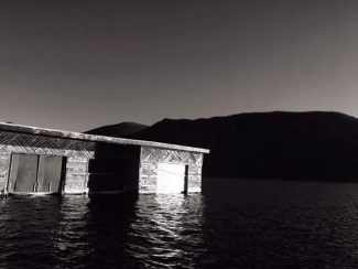 A rustic boathouse appears to float solemnly on Grand Lake, at sunset on Nov. 15.