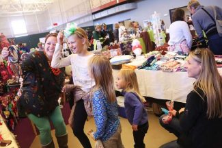 Locals Adrianna, Sienna and January Clark look on as their friend Matylda Rozewicz tries on a head band with help from business owner Amanda Rosenfried during the 18th annual Holiday Artisan Fair held at Grand Park Recreation Center in Fraser on Saturday, November 19. Vendor fees from this event benefit Fraser Valley Metropolitan Recreation District youth programs.