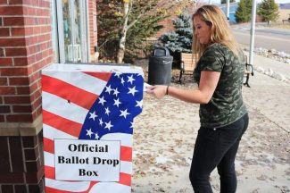 Senior Makenna Green puts her ballot in the drop box on Saturday, October 29.