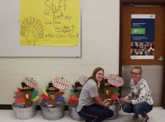 """Seniors Jene Hansen (left) and Erin Emery (right) contribute to the """"Stuff the Turkey"""" food drive that Middle Park High School is holding for Mountain Family Center on Tuesday, November 8. Each grade level is having a contest for class points for whoever can collect the most food."""