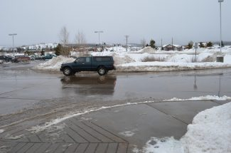 A truck drives through a puddle in the parking lot of Safeway in Fraser.