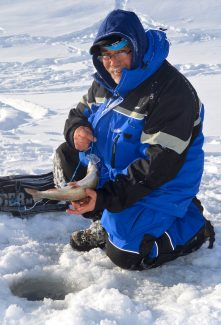 John Ota pulls a rainbow trout up out of the ice after catching the fish Jan. 27.