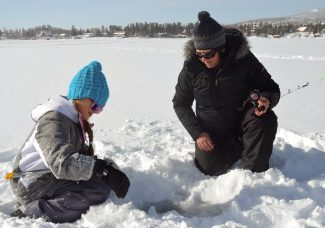 Little Sorina Scohy (left) and her mother Christina hurry to scoop ice out of a fishing hole Friday morning so they can drop their lines.