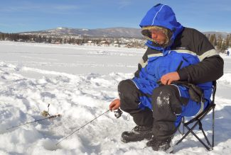 Jacob Griffith of Boulder works his line on Grand Lake Sunday during the Three Lakes Ice Fishing Contest.