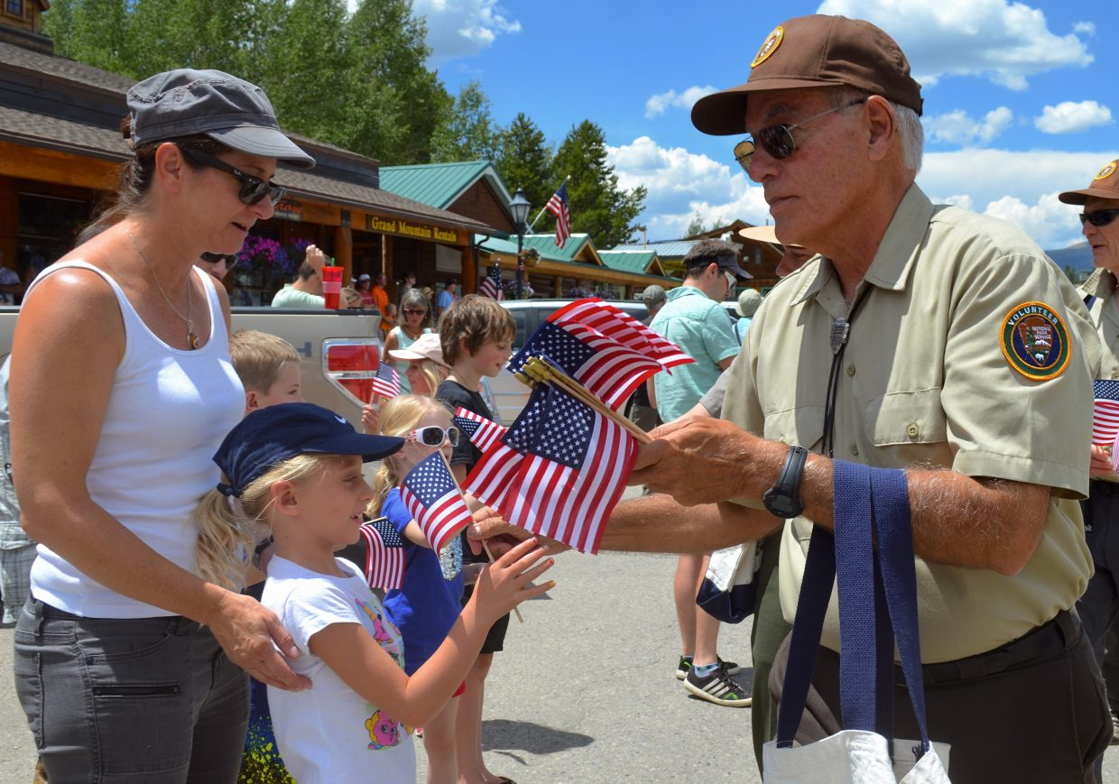 Rocky Mountain National Park volunteer Eduardo Orozco hands out American flags to folks attending the Grand Lake's annual Buffalo Days Parade Sunday afternoon.