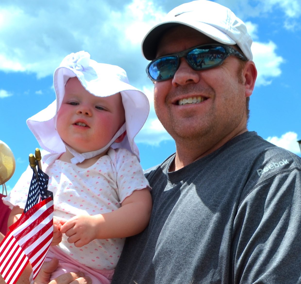 "Denver resident and Granby area homeowner Jeff Johnston holds his baby girl Macy while watching the Buffalo Days Parade. Johnston called Sunday's event the ""coolest parade I have ever been to."""