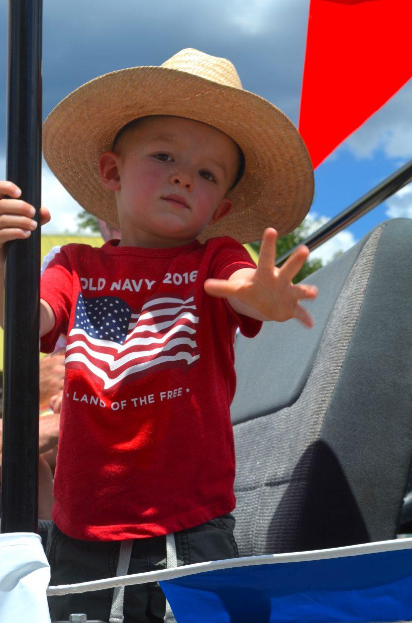 Young Brady Aucker waves to the camera as he rides on the Mountain Parks Electric Float in the Buffalo Days Parade.