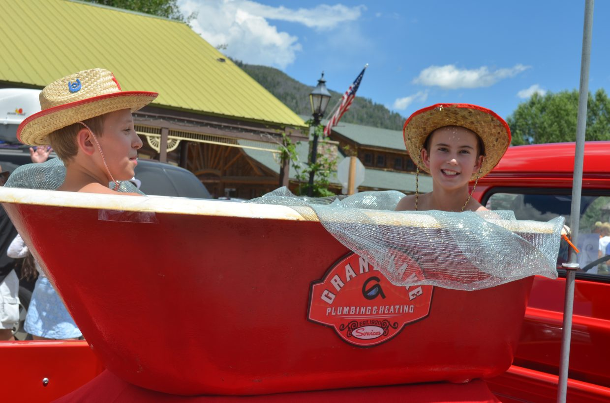A couple of youngsters take a faux bath while riding in the Grand Lake Plumbing & Heating float during the parade Sunday.