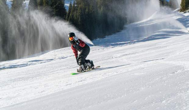 Skiers and riders made the first tracks of the season, while snow machines in the background continue to work hard.