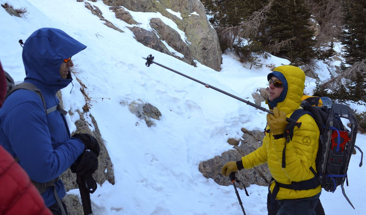 Adam Baxter, mountain guide and course instructor for CMS, explains some of the finer points of route selection to student Aaron Oakley as the pair discuss ice climbing opportunities in Rocky Mountain National Park.