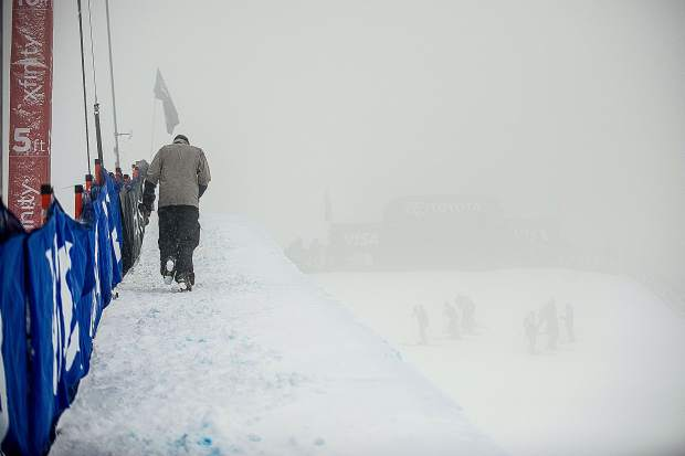 Photographer Drew Lederer braces the elements walking up the superpipe and the slip crew waits in the fog while the men's ski qualifiers were on a course hold due to weather at the U.S. Grand Prix competition on Wednesday.