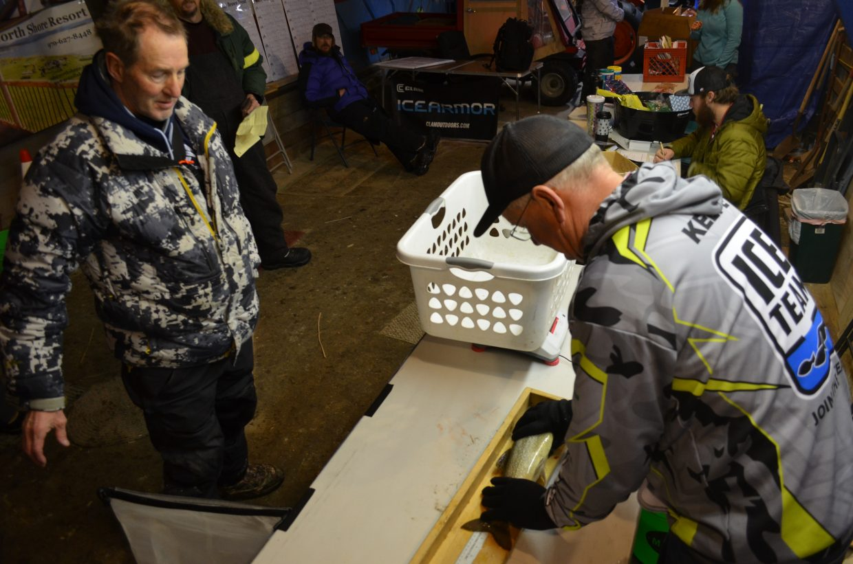 Grand Lake resident Gary Billiet (left) waits and watches as Three Lakes Contest weigh station operator, and local fishing guide, Bernie Keefe gets the measurement of his catch. Billiet was the first angler to submit a fish at the contest's weigh station Friday morning.