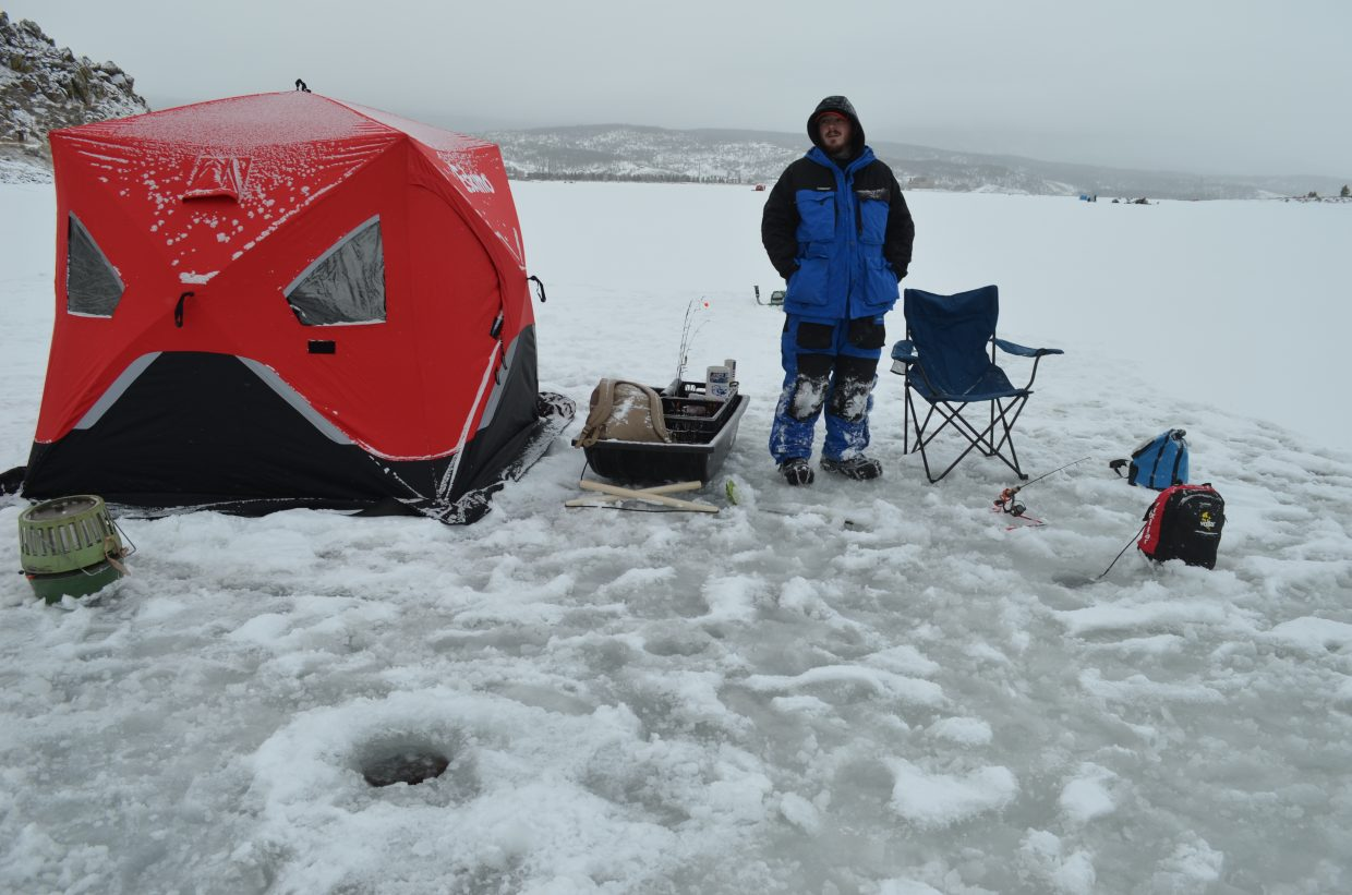 Russ Hurley, with Ice Fish Colorado, stands outside his fishing hut while waiting for a bit during the Three Lakes Ice Fishing Contest.