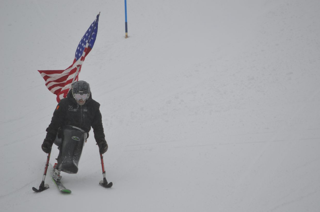 As Taulman sang, a sit-skier with an American flag made his way down the slalom course.