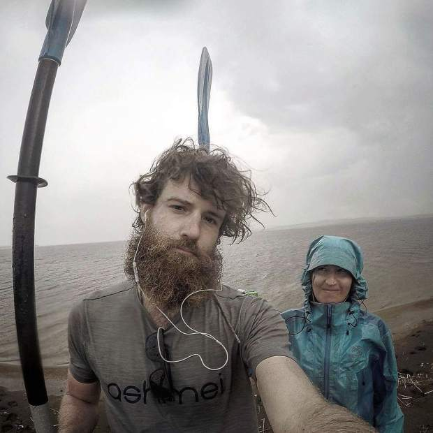 Callie Morgigno of Leadville and Charlie Walker of England pose for a photo with their kayak paddles despite rain on the Ural River in Russia.