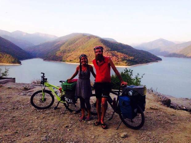 Callie Morgigno of Leadville and Charlie Walker of England pose for a photo with their bikes beside a lake in Georgia.