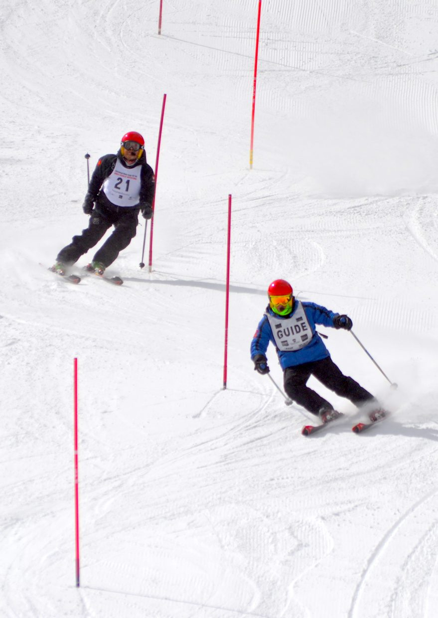 A ski racer (above) and ski guide cruise down the race course Sunday at the Wells Fargo Ski Cup.