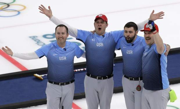 The United States team celebrates during the men's curling finals match against Sweden on Saturday.