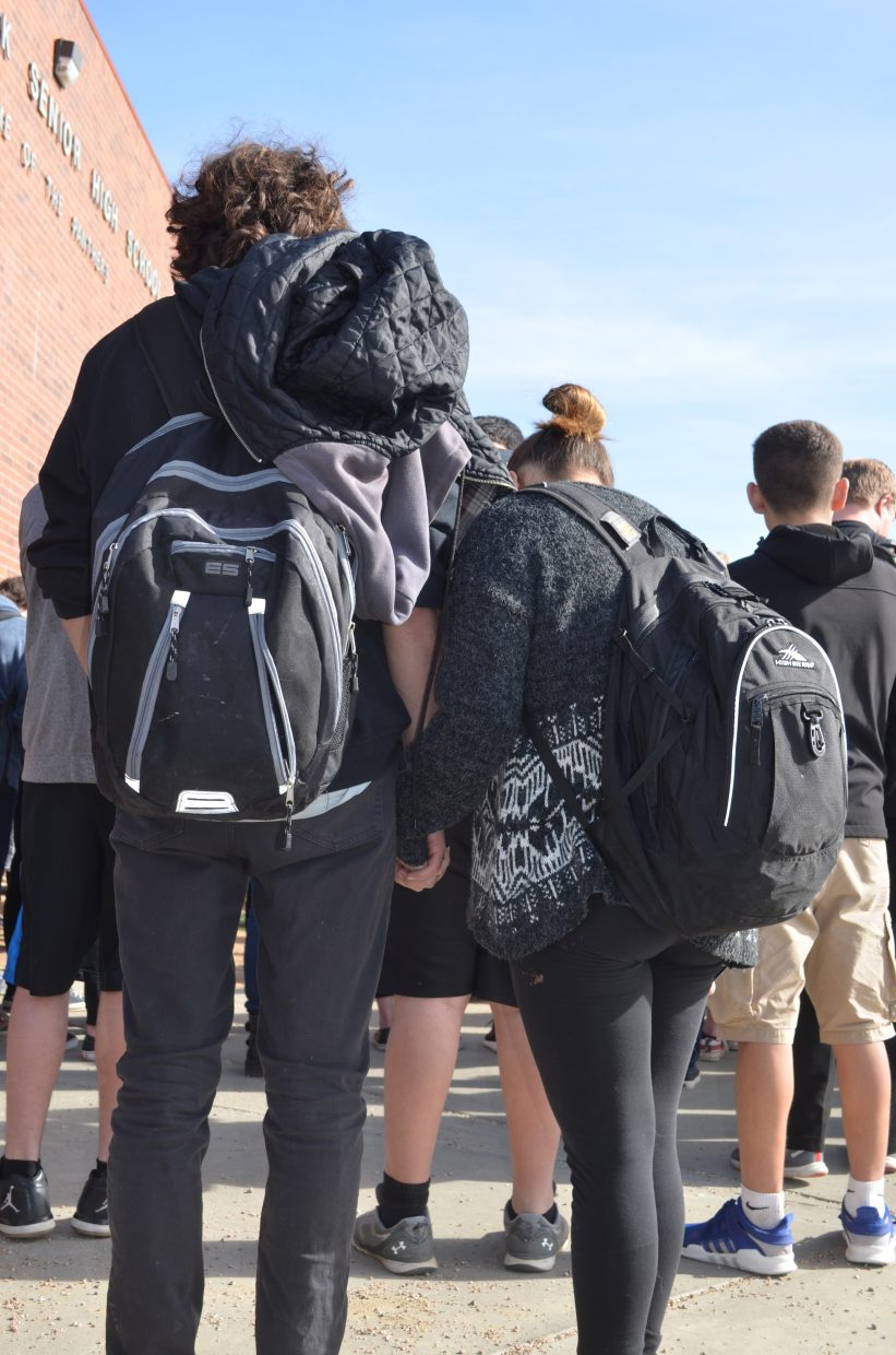 Two students hold hands during the walkout.
