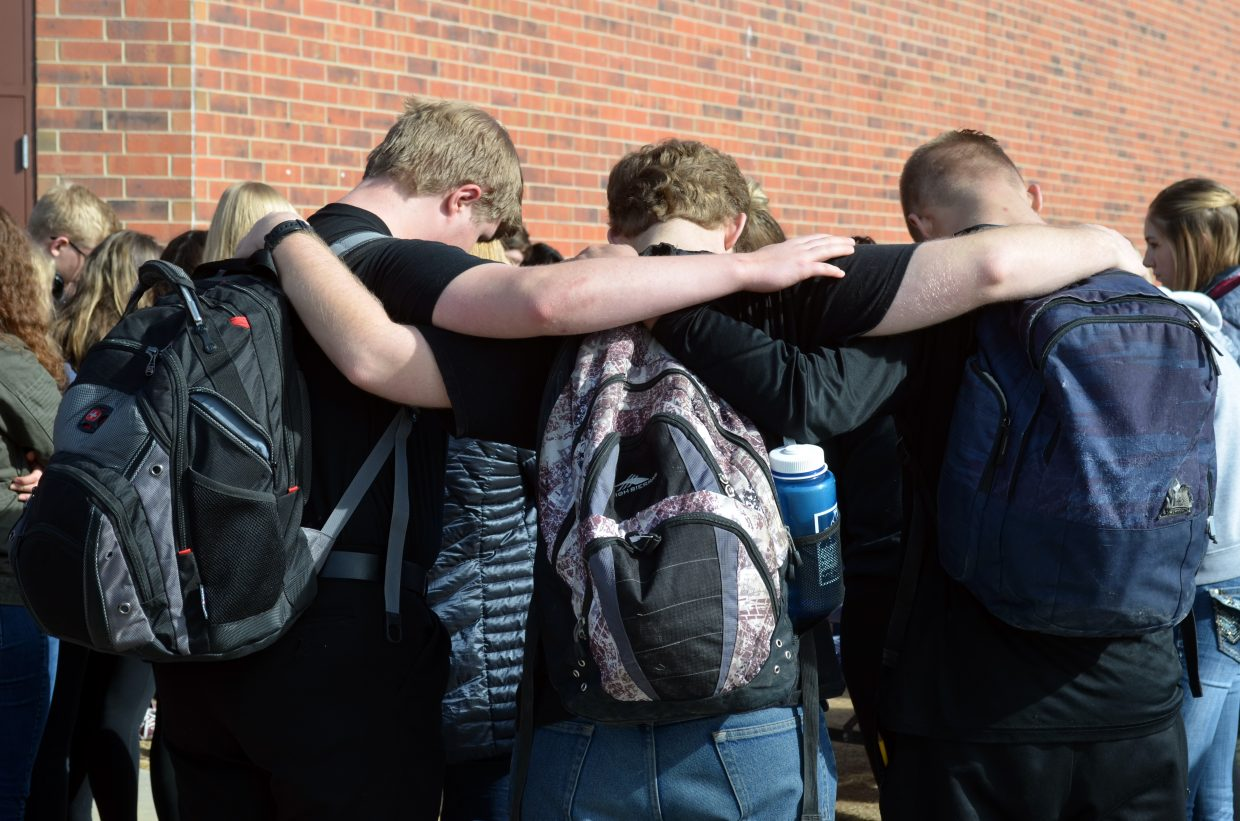 Three male students support each other Wednesday in front of Middle Park High School.