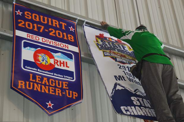 Coach Luke Steckler hangs the state championship banner in the Icebox hockey arena in Fraser.